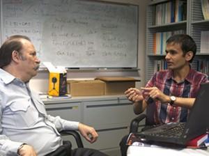 Kuldeep Meel (right) explains a solution to his adviser, Moshe Vardi