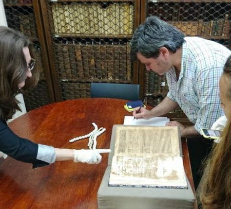 thumnail image of researchers examining an aintque book