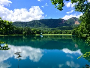 Reflections: A near perfect mirror image captured in the volcanic lake's turquoise water. ~ Haihao Liu