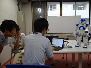 The three senseis, Araki-sensei (materials), Yoshimoto-sensei (circuits), and Uemura-sensei (processes) hard at work. Here we are trying to control Nao-kun the robot with our brain waves. ~ Donald Swen