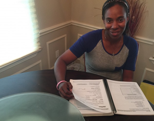 Caraway signing the paperwork to close on her home.