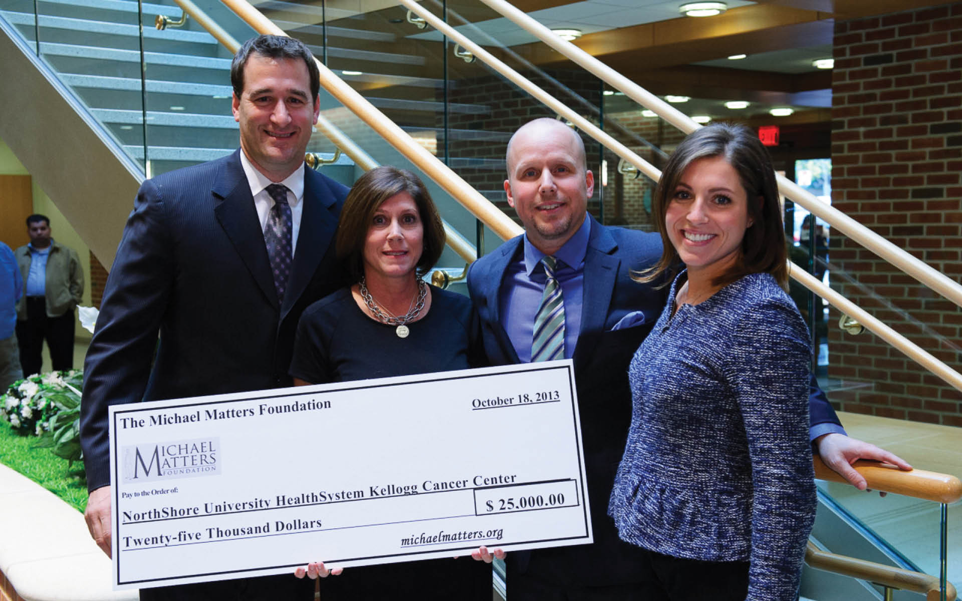 A check is made to the NorthShore University HealthSystem's cancer center from the Michael Matters Foundation, started by Roosevelt alum TJ Saye, third from left.