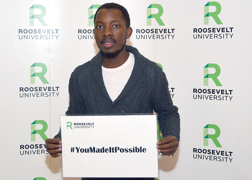Robert Rugamba holding #YouMadeItPossible sign
