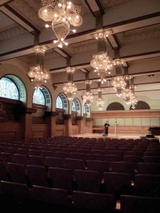 Ganz Hall with empty seats and a violinist on stage