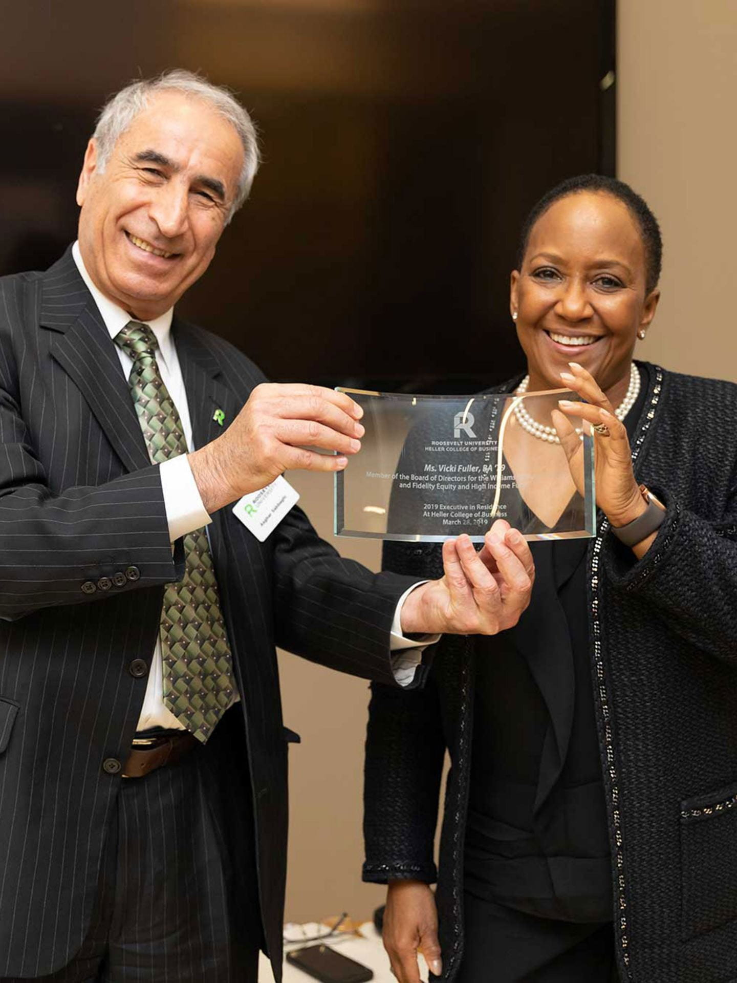 During Vicki Fuller's visit to Roosevelt University, Heller College of Business Dean Asghar Sabbaghi presented her with an award recognizing her storied career and contributions.