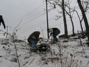 Conor and Chris drag a heavy tire up the steep slope from the river's shoreline