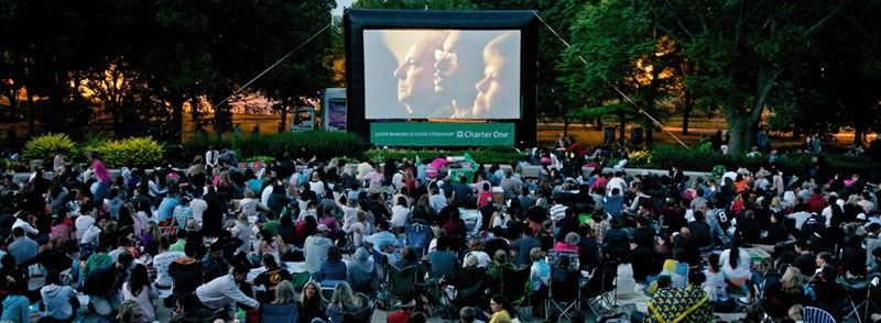 People sitting on lawn watching a film on a large backdrop