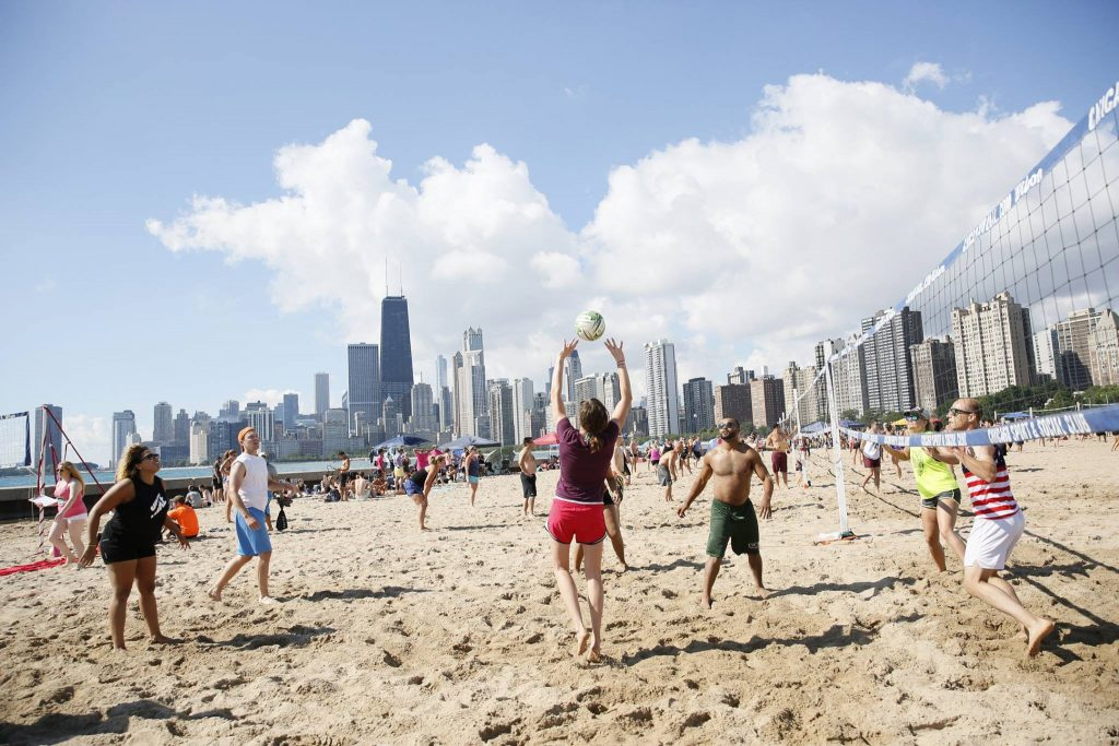 People playing sand volleyball with cityscape in background