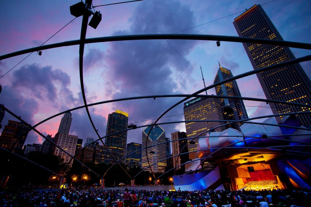 Audience sitting on lawn at Pritzker Pavilion listening to a concert