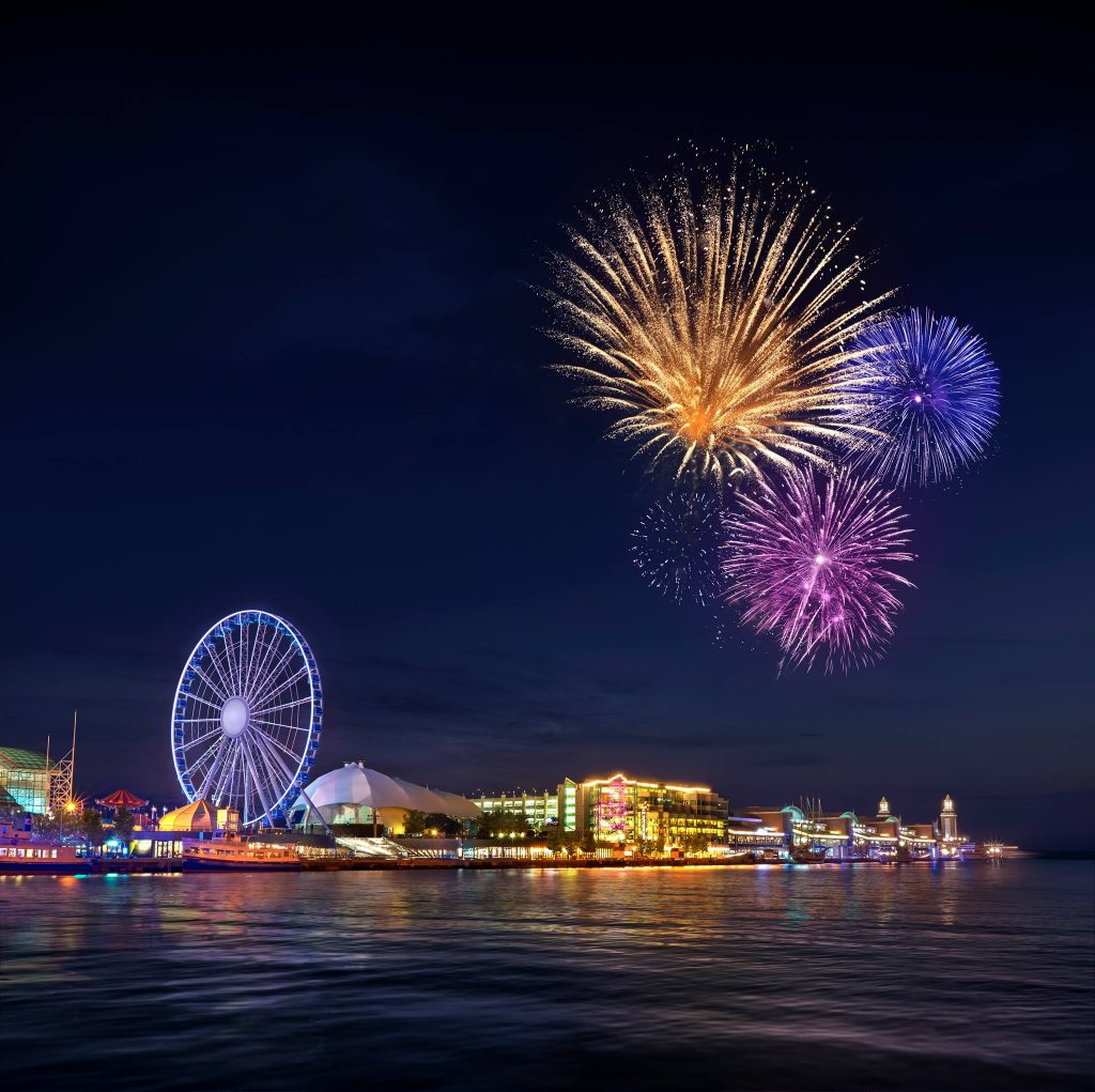 Navy Pier lighted up at night with ferris wheel spinning and fireworks in the sky