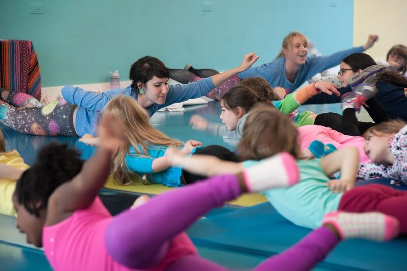 Warshaw practicing yoga with a group of girls as part of Mission Propelle
