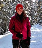 Ellen Aster standing in a snowy forest.