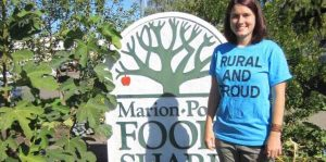 Student standing in front of a Food Bank sign
