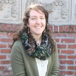 Photo of program coordinator smiling in front of a brick wall