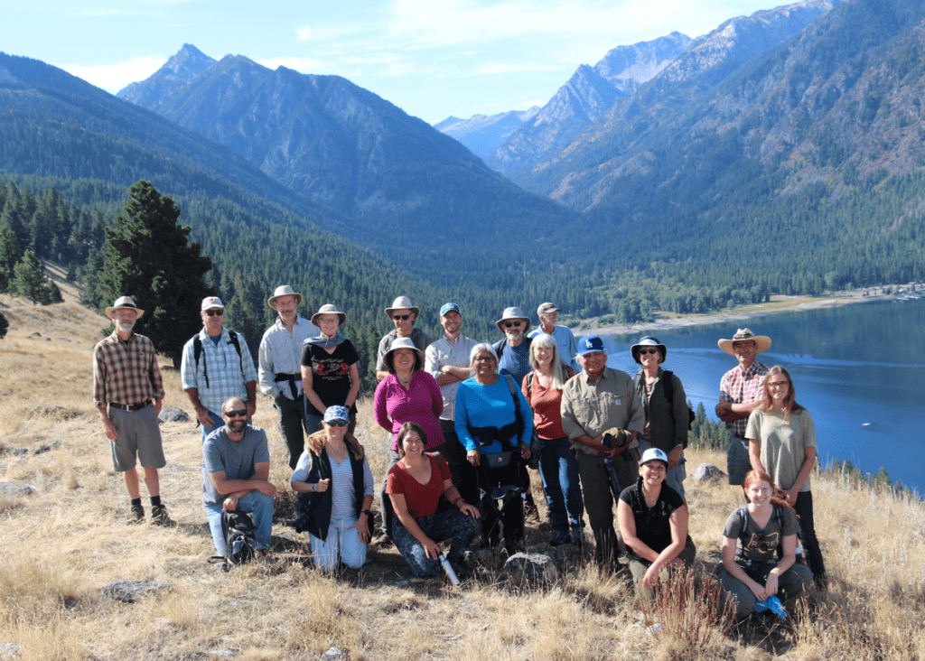 Group of people described in the article atop the East Moraine on a sunny day. There are many smiling faces. The lake and the Wallowa mountain range is present in the background. Dry summer grass is in the foreground.