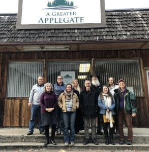 Group of happy people posed in front of the new building for A Greater Applegate