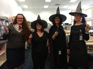 Four women dressed as witches. Three are wearing black and have pointy hats, the fourth is dressed like a Hogwarts student from the Harry Potter series. They all have wands.