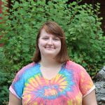 Photo of the author. She is wearing a bright tie-dye shirt and standing in front of a red flowering currant.