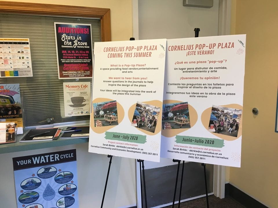 "Two informational boards, one in English and one in Spanish, promoting an event called ""Pop-Up Plaza"""