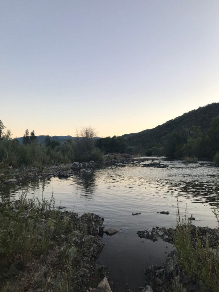 Photo of a serene body of water during twilight. There are many large rocks in the water and a hill in the distance.