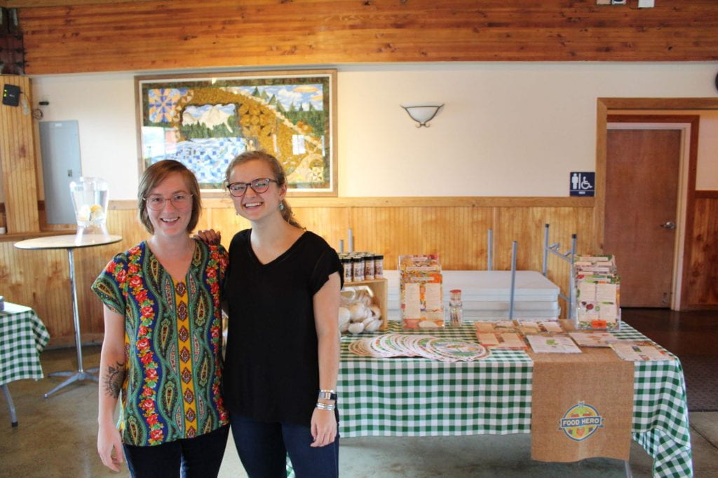 Author and fellow RARE member standing close together in front of a Food Hero display table