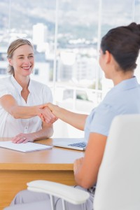 Cheerful interviewer shaking hand of an applicant in her office
