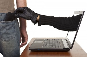 Internet theft - a gloved hand reaching through a laptop screen