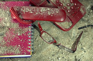 Broken phone, notebook and glasses, in the dirt and covered in dust