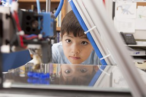 Boy intently watches 3D printer