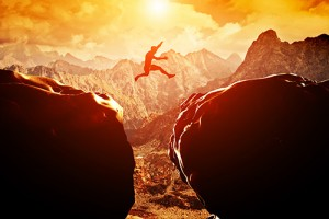Man leaps across a precipice in the mountains at sunset.