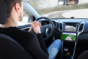 Stock photo of a young man clasping his hands near the steering wheel of a self-driving car.