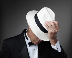 Dapper man in white fedora, face partially obscured.