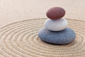 Photograph of three stones stacked in the center of a pattern raked into the sand of a Zen garden.