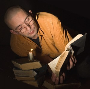 Photo of a man reading a book by candlelight.