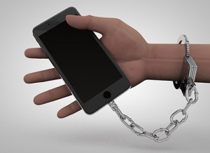 Photo of cell phone chained to a human hand.