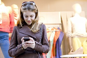 Photo of a young woman in a clothing store looking at her phone.