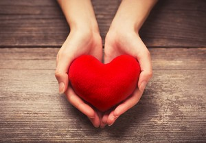 Photo of hands cradling a decorative red heart.