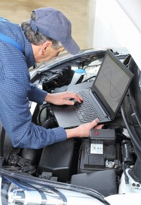 Man uses a laptop computer to examine a car engine.