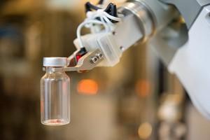 Robot holds medical vial.