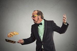 Photo of man flipping pancakes.