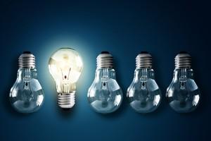 Photo of lit lightbulb facing opposite direction of unlit bulbs.