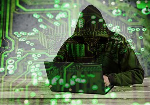 Stylized photo of a hooded hacker at a laptop.