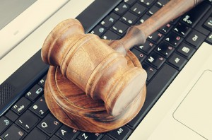 Photo of wooden gavel on a black computer keyboard.