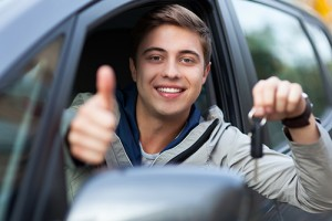 Photograph of smiling teen boy sitting in a car, flashing a key and a thumbs up.