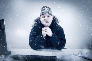 Photo of a man wearing a hat and parka, sitting at a desk in a snowstorm.