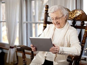 Photograph of smiling elderly woman using a tablet computer.