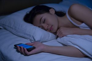 A woman sleeps clutching a smart phone.