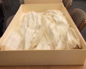 Acid-free paper was placed below and in between to skirt to prevent further folding.