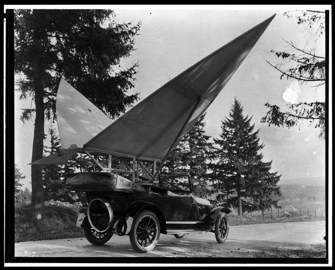 Early automobile with large sail wings attached to it labeled 'Moon Car'