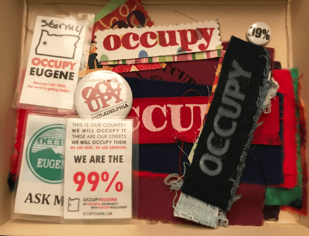 Buttons, pins, name badges related to Occupy Eugene